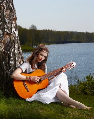 9971074-outdoor-portrait-of-beautiful-hippie-girl-sitting-on-green-grass-near-birch-with-guitar-lake-and-for